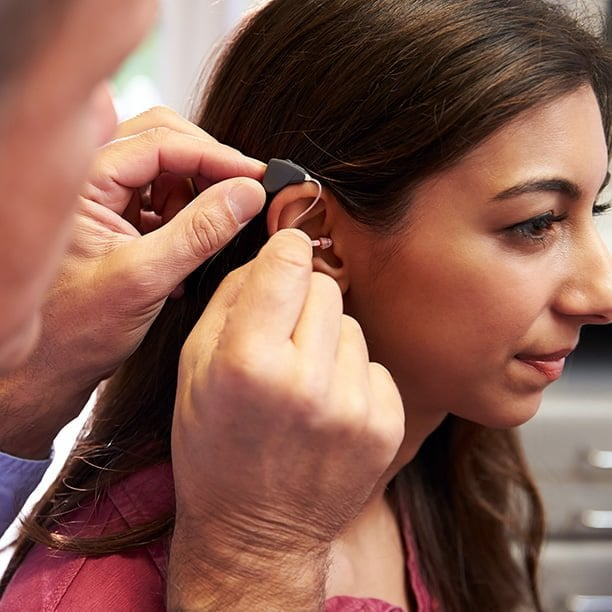 young female being fitted with a behind the ear (BTE) hearing aid