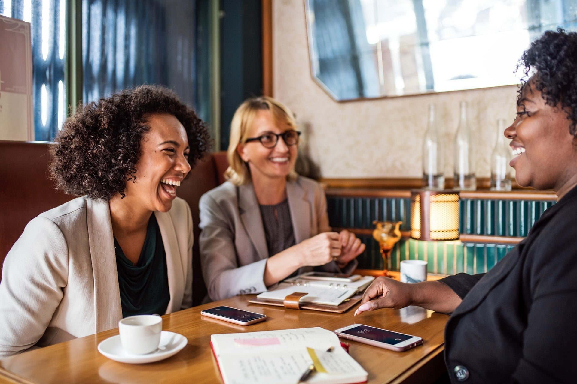 three women sitting at a restaurant table conversing and laughing