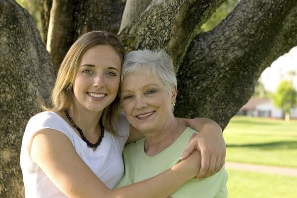 Daughter holding mother standing in front of a tree smiling