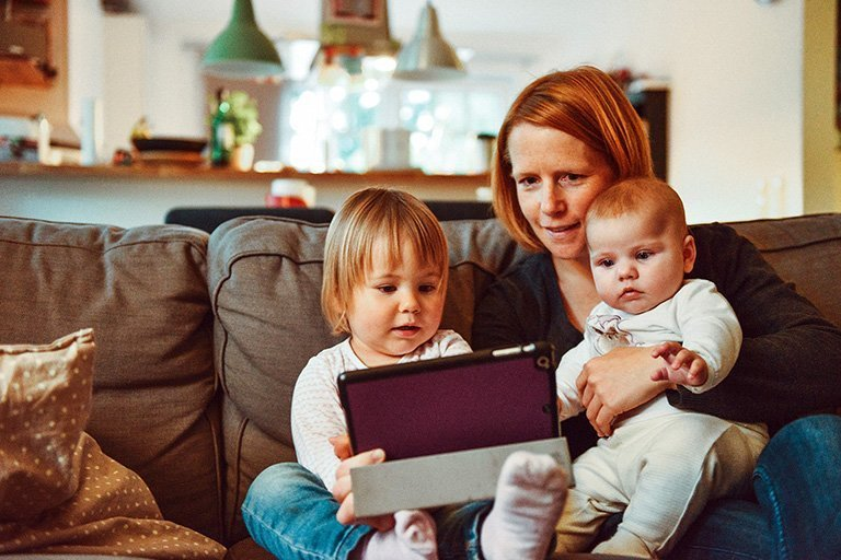 Mother with two young children sitting on a couch looking at a tablet
